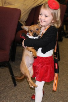 A child brings her Christmas puppy forward for the blessing.